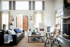 Country superstar Ronnie Dunn's living room features towering white wingbacks and an impressive antler chair which demonstrate the home's cozy-and-inviting meets rough-and-tough aesthetic. The corner table (far right) was a wedding gift from June Carter and Johnny Cash.