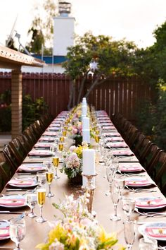 table for 32 16 on each side reception seating, yellow, pink, white candles, wooden chairs
