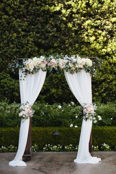 Blush and white wedding arch at Franciscan Gardens. Draping fabric curtains with roses, eucalyptus, ranunculus. -Florals by Jenny