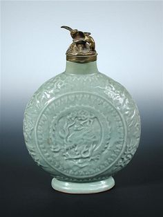 A 17th/18th century celadon moon flask and European gilt metal cover, moulded with a dragon on one side and a phoenix on the other enclosed by foliage, 23.5cm (9.25 in) high (2) (R)