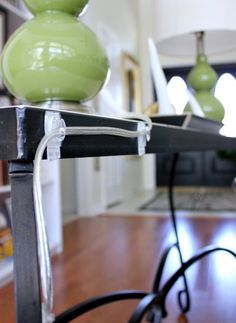 disguise lamp cords by threading  through a series of Command hooks placed along the back of the table, and down the leg.