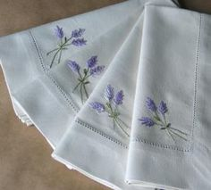Embroider a set of napkin with a lavender motif in hand embroidery. I've used variegated floss in this simple design, which uses just two basic surface embroidery stitches.
