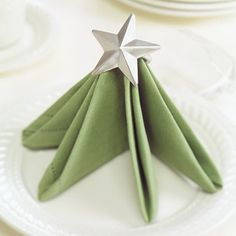 Star-Top Tree Napkin  With a few creative folds, this festive tree napkin topped with a silver star will impress guests.