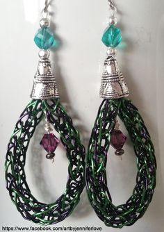 Viking knit earrings made with 22 gauge green and purple silver filled wire, with swarovski bicone crystals in purple, multifaceted crystals in teal, and silver plated cones.