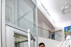 Dr Chelvi Kumar and Sathia Kumar with the glass lift at the centre of their recently completed home.