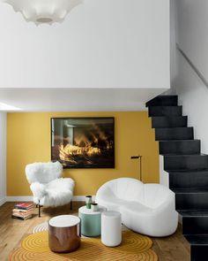 Γγρ│ Mur du fond et tapis moutarde, escalier noir, donnent une note moderne et chic à cet appartement blanc.