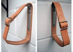 Shelf brackets made from custom leather belts with buckles and an aluminum fastening to mount onto wall