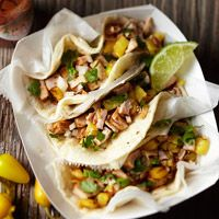 These street-vendor tacos combine pork and pineapple cooked on a vertical spit. The meat is carved off along with bits of pineapple. Try a  home-cooked version of tacos al pastor that calls for grilling slices of pork loin and fresh pineapple. And of course, top with avocados.