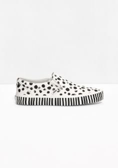VANS Crafted from leather, these classic slip-on shoes are detailed with dots, stripes and a textured finish.
