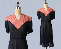 Late 1930s or early 40s day dress is gorgeous sheer lightweight navy blue silk. Yoke features v shape in front and back, and is fashioned in pink silk. Lightly padded shoulders and short sleeves. Metal side zip. Gored skirt with wonderful shape and movement. Ruched shoulders and snaps at left shoulder. Measurements: Recommended size M-L -Bust: 38 -Waist: 29 -Hip: 42 -Length: 41  Condition: Excellent. Some faint lines across shoulders, not noticeable.  **All items $100+ are available for…