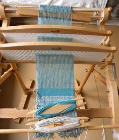 Le métier est installé pour réaliser du tissage double : deux peignes, deux baguettes à l'arrière, et les deux navettes.