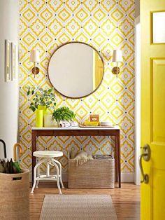 baño con papel pintado de motivos geométricos en color amarillo y gran espejo circular