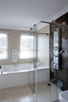 O banheiro planejado pelo arquiteto Rogério Perez, em um refúgio de veraneio, possui 12,45 m² e abriga áreas de chuveiro-spa e de hidromassagem. Bem iluminado, o espaço passa a sensação de amplitude. No detalhe, as pastilhas escuras contrastam com o tom claro das paredes, do piso, dos gabinetes e das louças
