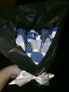 Baby socks rolled, double sided tape to hold them, ribbon to cover tape, straw cut to any size needed, vase/mason jar, tissue paper, done! Baby Sock Bouquet!