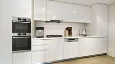 Cocina lineal blanca con equipamiento Bosch, horno y horno microondas embutidos anafe a gas, cafetera, campana integrada, lavavajillas integrado con panel frontal y heladera con refrigerador.