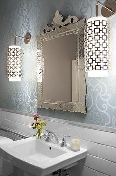 Beautiful bathroom design with Venetian mirror, white pedestal sink, blue wallpaper, Jonathan Adler Parker pendants and white subway tiles backsplash.