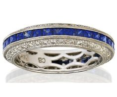 SAPPHIRE AND DIAMOND RING, BUCHERER Designed as a continuous row of channel set carré cut sapphires between borders of round brilliant cut diamonds, mounted in 18ct white gold, with maker's mark CB for Bucherer, Switzerland.