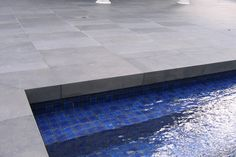 Bluestone Paving with blue pool tiles. Note paving over pool lip