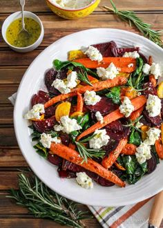 Roasted Beets and Carrots Salad with Burrata | Overhead shot of platter of roasted carrots, beets, and greens salad with burrata on dark wood background. | The Noshery
