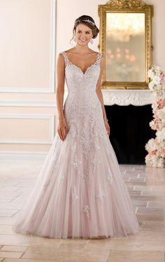 This sparkling silver lace wedding dress from Stella York is sure to be a show-stopper! The modern modified A-line silhouette boasts metallic lace that flows down from the Diamante covered bodice onto a light-as-air tulle skirt. The sweetheart neckline and illusion lace straps create an organic-edge neck that will flatter any bride-to-be! Sparkling crystal bead work brings attention to the bride's face while the tulle skirt adds drama and dimension to the look. Available in plus sizes.