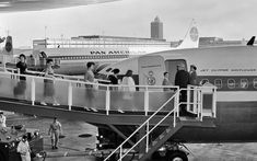 """Pan Am passengers boarding the """"Jet Clipper Mayflower"""", a Boeing 707-121 (tail number N711PA, formerly named """"Clipper America"""") at the Pan Am Worldport at Idlewild Airport (now John F. Kennedy International Airport), early 1960s."""