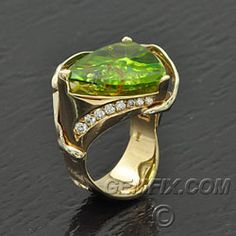 American Made. Large, shield shaped peridot with intrusions of red coral, lapis lazuli, and turquoise. Weight is 9.92 carats and measures approximately 17 x 15 mm.14KT yellow gold ring crafted by San Diego jewelry designer Ming. High polish gold is accented with 8 diamonds, and fluid scroll cutouts along the sides. Ring is handmade, one of a kind and is a size 6 1/2. Price: $2,200 Gemfix
