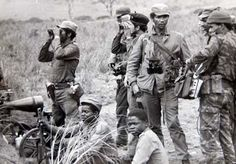 Angolan and Cuban soldiers confer somewhere in Angola. Precise location and year unknown.