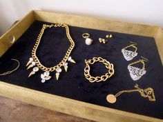 Make this DIY jewelry case out of repurposed items for a stylish way to display your accessories!