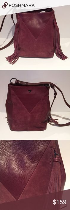 Sam Edelman Port Wine Monica Bag A stylish mix of leather and suede in this boho inspired bag. It has trendy fringe zippers and a cross body, bucket style. It is ideal for weekday to weekend looks. It is 9 1/2 in. wide, 12 in. high, and 6 in. deep. The strap is 21 in. long. The bottom has four gold-tone feet. There are 2 exterior zippers, one interior zipper, and 2 slip pockets. Sam Edelman Bags Crossbody Bags