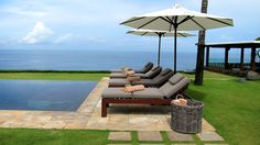 Lounge by one of the 2 infinity pools overlooking the ocean at The Istana, a clifftop estate in Bali, Indonesia.
