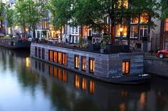 A large shingled houseboat in Amsterdam with a variety of potted plants and patio furniture on the roof. Houseboat Living, Houseboat Ideas, Lakefront Property, Canal Boat, Floating House, Belle Villa, Narrowboat, Tiny House Movement, Boat Plans