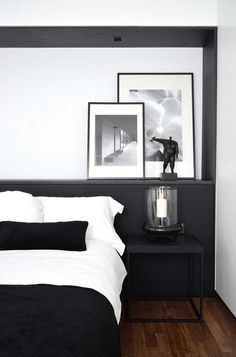 Modern and minimalist black and white bedroom with matte dark gray painted walls, a built-in shelf behind the bed with a leaning gallery wall of framed photographs, open glass hurricane vase with candle, crisp white bedding, sleek black nightstand and black velvet lumbar pillow for a dose of luxury and texture.