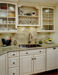 granite top/antique ivory cabinets/dark floor combo love the black splash for the retrish kitchen