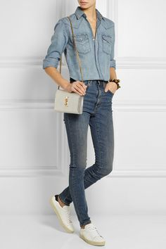 SAINT LAURENT Denim shirt; High-rise skinny jeans; Court Classic leather sneakers; Monogramme small metallic leather shoulder bag