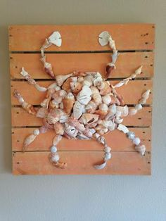 22''x22'' crab made of broken seashells on a distressed wood pallet