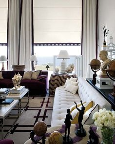 Patterned rug, console table behind sofa, round skirted tables, vignettes, black and white with pops of color