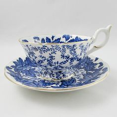 Beautiful tea cup and saucer set is made in England by Coalport. Tea cup is white with a blue pattern and gold trimming with matching saucer. Teacup and saucer in great condition with no chips or cracks, but there is some fine crazing on the handle of the tea cup (see photos). Markings