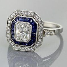 Art Deco Platinum Milgrain ring featuring 1.23 Carat Radiant Cut Diamond center bezel set consisting of 20 Specialty Cut Sapphire Gem Stones equaling 1.22 Ct. Channel set & 39 Pave Brilliant Rounds equaling 0.28Ct.