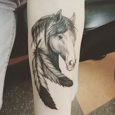 Pretty horse tattoo with feathers.