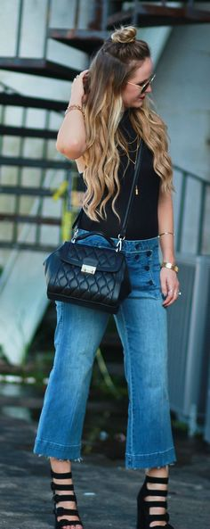 A fall transition outfit styled with a mockneck black bodysuit, frayed culotte jeans, cage heels, and Ray Ban Icon sunglasses