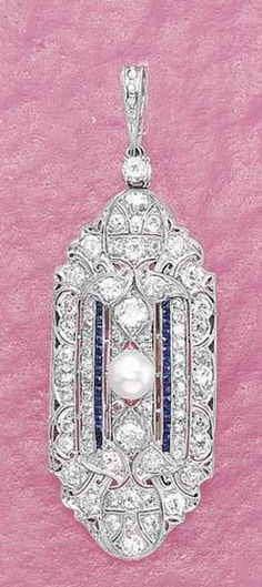 An Art Deco Sapphire Diamond and Pearl Pendant/Brooch  The openwork plaque entirely decorated with circular-cut diamonds to the two rows of square-cut sapphires set to the center with a pearl, mounted in platinum and 14K white gold.