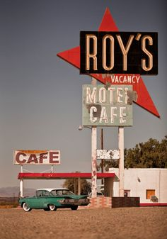 Roy's Motel and Cafe. Green car with tailfins parked on the parking lot. Awesome vintage sign!