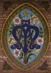 Detail of an enamel on the front of an altar in the Rosary Basilica of Lourdes with the monogram: 'Ave Maria'.