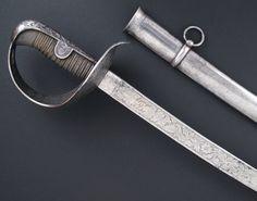 """R-88113.- Sable """"a capricho"""" de oficial de Caballería. España, fechado 1854. Guarnición en acero """"a la prusiana"""", enteramente grabada,  incluyendo el interior de la cazoleta. Puño de madera forrado en piel de lija y afirmado mediante alambre de alpaca. Hoja curva, adornada en su primer tercio con grabados decorativos. Marcada """"ARTa Fa de Toledo"""" - """"1854"""". Plana en su primer tercio, semivaceo en el medio, pala en sección lenticular. Vaina de hierro con dos anillas."""