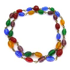 A lovely string of beautiful Gripoix glass beads in vibrant rainbow tones. The beads are on base metal chain links and the necklace is finished...