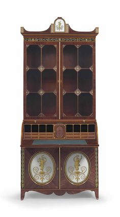 A FEDERAL SATINWOOD-INLAID AND VERRE EGLOMISE MAHOGANY CYLINDER DESK-AND-BOOKCASE PROBABLY BALTIMORE, 1800-1810 the base doors open to a divided interior fitted with short drawers and central folio section, the lowermost drawers with lidded compartments... Price Realized $567,750 Set Currency Estimate $150,000 - $300,000