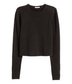 Musta. Lyhyt ja ohut neulepusero, jossa pitkät hihat ja korkea selkähalkio.