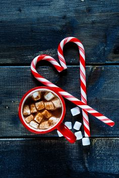 Hot dark chocolate - Top view of traditional hot chocolate with marshmallows and candy sticks over dark texture background. Christmas drink theme.