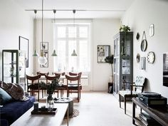 Bright Scandinavian home with a dark blue sofa, and industrial pendant lights