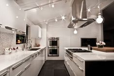 sleek lines repeated in lighting, cabinets, appliances and hood